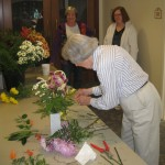 "Karen and Peggy watch Jane B. execute speed flower arranging at Foulkeways. Jane also frequently does a very large arrangement for ""the Niche,"" which commemorates those Foulkeways residents who have died in recent weeks."